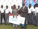 Pepsi Brand Executive Tracy Kakuru (with dummy cheque) watches on as the Uganda Cricket Association CEO, Justine Ligyalingi,
