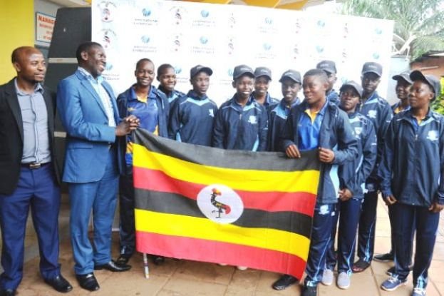 Keep The Flag Afloat. NCS' Katende (2nd L) and Ondeko (L) saw off the young girls cricket team to Kigali yesterday. PHOTO BY EDDIE CHICCO